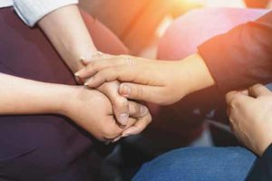 hand reaching supportively to another at addiction treatment programs