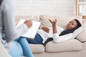 woman on couch and therapist discussing heroin detox center program oklahoma city