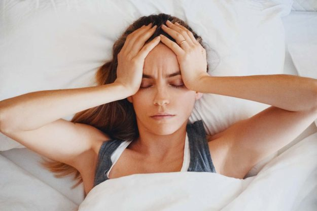 woman with hangover holding head in bed showing signs of alcoholism