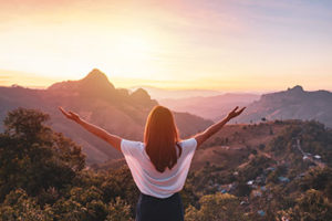 woman spreading arms and looking towards a desert sunrise after leaving opiate addiction treatment center